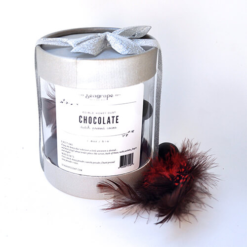A cylindrical clear box holds the Chocolate Honey Dust, with a handmade feather applicator next to the box.
